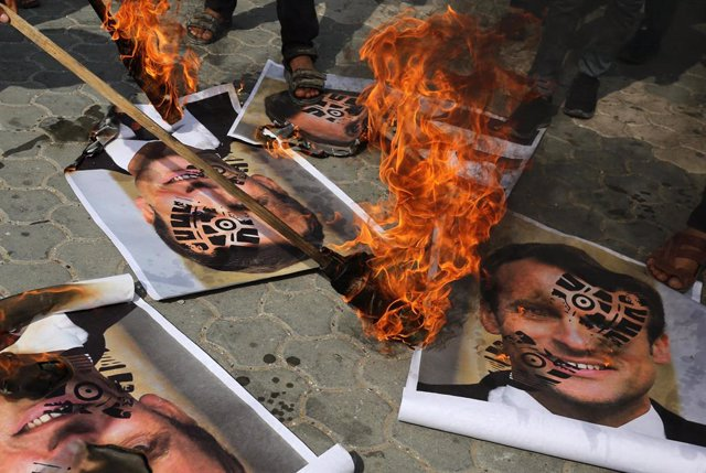 30 October 2020, Bangladesh, Dhaka: Bangladeshi Muslim protesters burn pictures of French President Emmanuel Macron during a demonstration against his comments on Islam's prophet Muhammad cartoons. Photo: Ashraf Amra/APA Images via ZUMA Wire/dpa