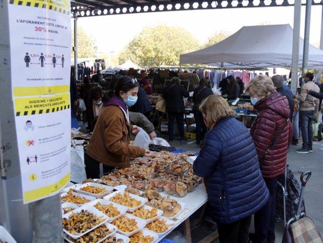 Pla obert de dos cartells al mercat de Barris Nord de Lleida amb les mesures de seguretat que s'han de seguir al recinte, i al fons hi ha dos clients comprant bolets, el 31 d'octubre de 2020. (Horitzontal)