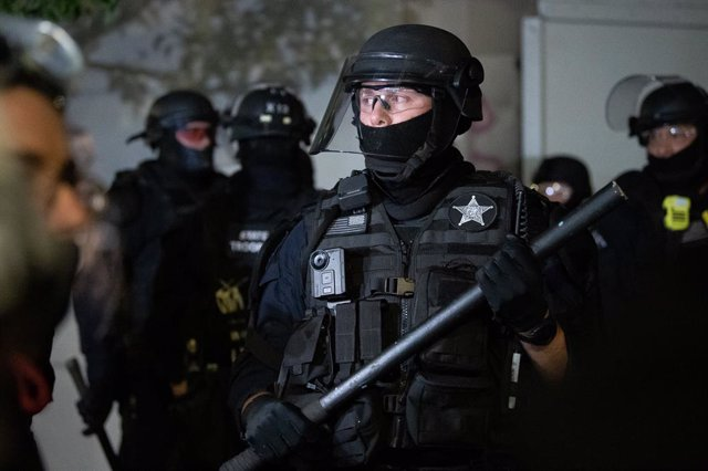 04 September 2020, US, Portland: An Oregon State Trooper holds a baton as officers and protesters square off in front of the Portland Police Association building on North Lombard and North Campbell Streets, as Black Lives Matter protesters demonstrate aga