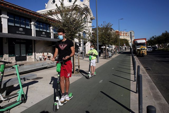 15 October 2020, Portugal, Lisabon: Two boys wearing face masks ride an electric scooter as Portugal declared a nationwide disaster on 14 October due to a sharp rise in coronavirus infections. Photo: Pedro Fiuza/ZUMA Wire/dpa