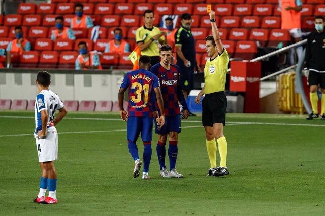 BARCELONA, SPAIN - JULY 08: the referee Jose Luis Munuera Montero showing yellow card to 31 Ansu Fati of FC Barcelona during the Spanish League, La Liga, football match played between FC Barcelona and RCD Espanyol at Camp Nou stadium on July 08, 2020 in B