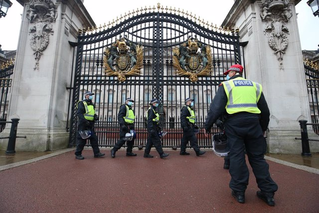 24 October 2020, England, London: Police officers with protective equipment gather at the gates of Buckingham Palace during a protest against the imposed lockdown restrictions to prevent the spread of coronavirus. Photo: Jonathan Brady/PA Wire/dpa