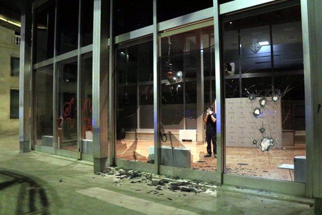 Un tècnic es mira els vidres trencats de l'Edifici Novíssim de l'Ajuntament de Barcelona, amb una pintada okupa, després d'una manifestació contra els desnonaments. 31 d'octubre del 2020. (Horitzontal)