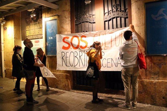 Pla general d'un grup de manifestants penjant una de les pancartes reivindicatives a les portes del Teatre Metropol de Tarragona en la protesta per reivindicar que la cultura és segura. Imatge del 31 d'octubre del 2020 (Horitzontal).