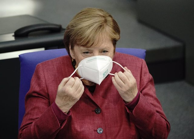 29 October 2020, Berlin: German Chancellor Angela Merkel removes her face mask as she arrives to attend a plenary session at the German Bundestag, where she will make a government declaration on how to cope with the coronavirus pandemic. Photo: Michael Ka