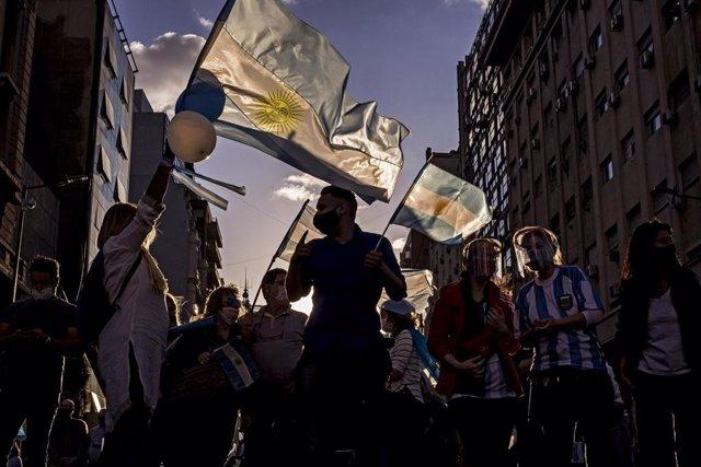 Manifestantes enarborlan banderas en una manifestación anti-cuarentena en Argentina.