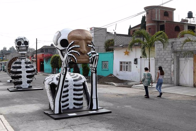 29 October 2020, Mexico, Mexico City: Passers-by walk near giant cardboard skulls at Francisco Santiago Borraz street which were placed for the Day of the Dead celebrations. Photo: -/El Universal via ZUMA Wire/dpa