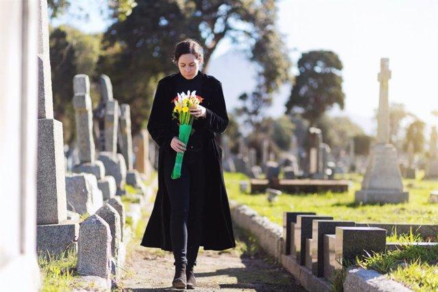 Mujer llevando flores a una tumba en un cementerio.