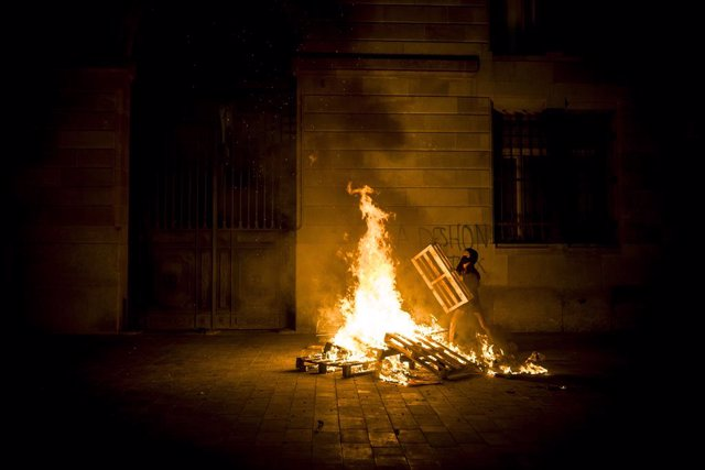 31 October 2020, Spain, Barcelona: Ademonstrator burn objects behind Barcelona's town hall during a protest against the eviction of Casa Buenos Aires. Photo: Matthias Oesterle/ZUMA Wire/dpa