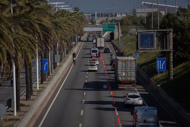Vehículos realizan cola durante un control de movilidad en la Ronda del Litoral dirección salida de Barcelona.