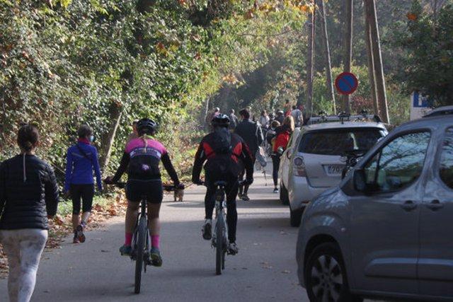 Pla mitjà de l'inici d'uns dels camins que porta al Castell de Sant Miquel amb cotxes, bicis i gent caminant aquest diumenge 1 de novembre de 2020. (Horitzontal)