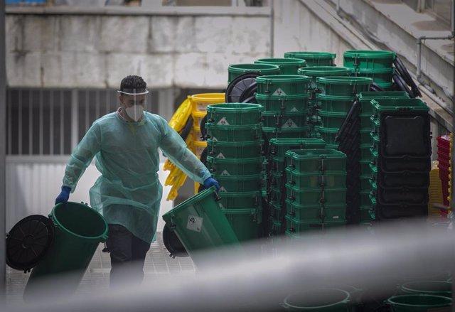 Un trabajador sanitario apila cubetas de residuos en el Hospital Virgen Macarena.