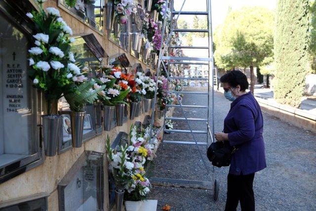Pla general d'una dona portant les flors a una sepultura al cementiri de Tarragona en la festivitat de Tots Sants. Imatge de l'1 de novembre del 2020 (Horitzontal).