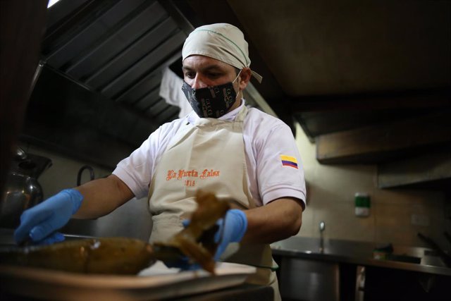 31 July 2020, Colombia, Bogota: A cook wraps a pie in a banana leaf at a restaurant as food services and snack bars are being allowed to resume operations gradually after three months of closure due to the coronavirus pandemic. Photo: Sergio Acero/colpren