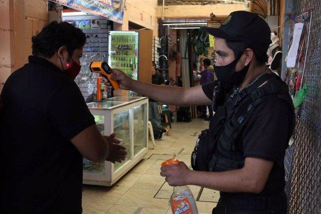 Un hombre se tomar la temperatura a su entrada al Mercado de Hidalgo, en Ciudad de México.