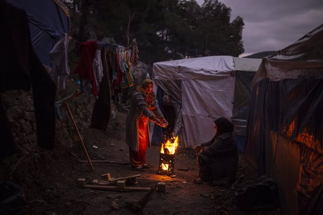 21 February 2020, Greece, Samos: Refugees warm themselves with a campfire in a refugee camp. The Greek government is building a new camp for refugees on the island of Samos. The camp will be able to accommodate 1,200 migrants. Photo: Angelos Tzortzinis/dp