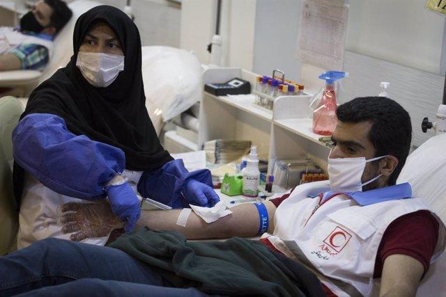 Una trabajadora sanitaria durante una donación de sangre en el marco de la pandemia de coronavirus en Irán
