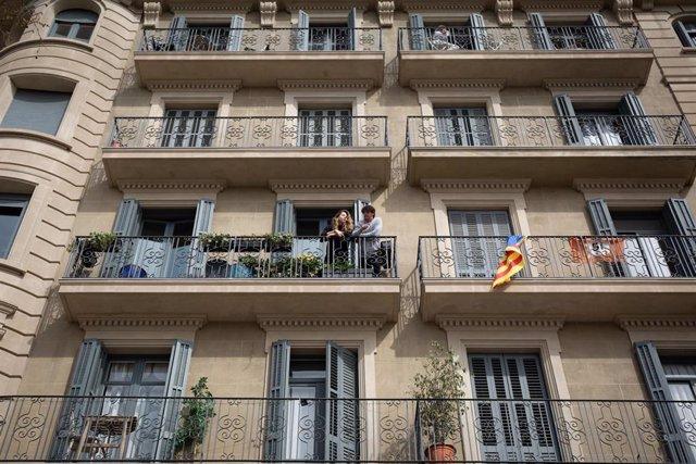 Dos personas se asoman al balcón durante el estado de alarma por coronavirus decretado en España durante la primera ola de la pandemia (Archivo)
