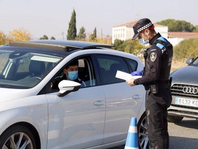Pla mitjà d'un agent de la Guàrdia Urbana mirant el paper justificant de mobilitat d'un conductor a un control a la N-230 direcció Lleida, el 30 d'octubre de 2020. (Horitzontal)