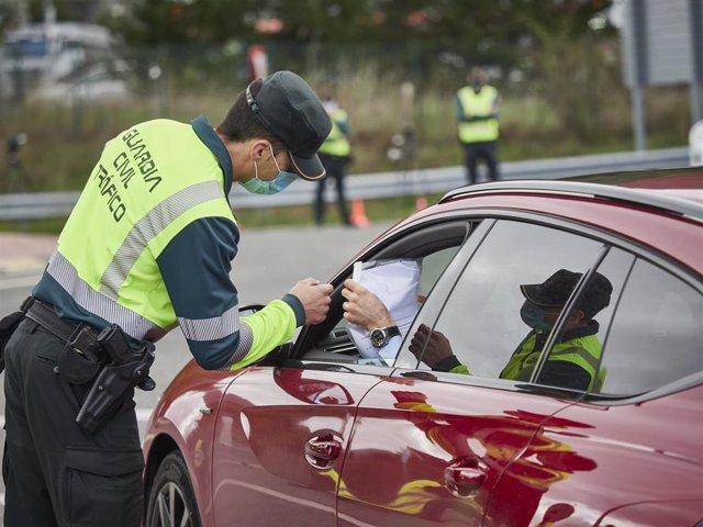 Un agente de la Guardia Civil de Tráfico comprueba la documentación de un conductor en un control policial