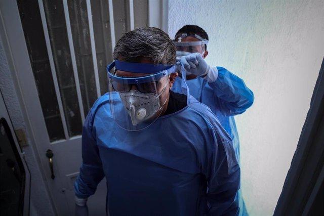 Dos trabajadores sanitarios realizando labores médicas en la lucha contra el coronavirus en Colombia.
