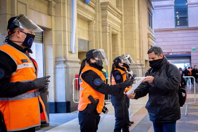 01 July 2020, Argentina, Buenos Aires: Police officers check documents of a passenger at the Constitucion railway station.  Argentina extends and toughens the quarantine in the Buenos Aires metropolitan area from July 1 until July 17 after coronavirus inf