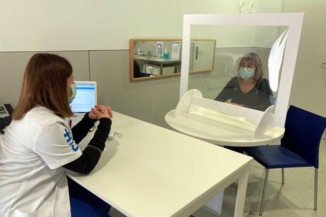 Pla general de la consulta d'una logopeda atenent una docent com a usuària darrere d'una pantalla de protecció el 3 de novembre del 2020 a Manresa. (horitzontal)