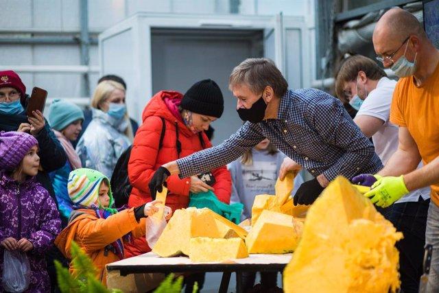 Empleados del jardín botánico repartiendo trozos de una calabaza gigante en Moscú