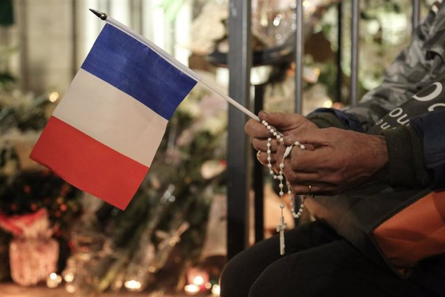 31 October 2020, France, Nice: A person holds the French National flag outside the Notre Dame basilica as people gathered there to pay their respect for the victims of the knife attacking which resulted in killing three people and injuring several others