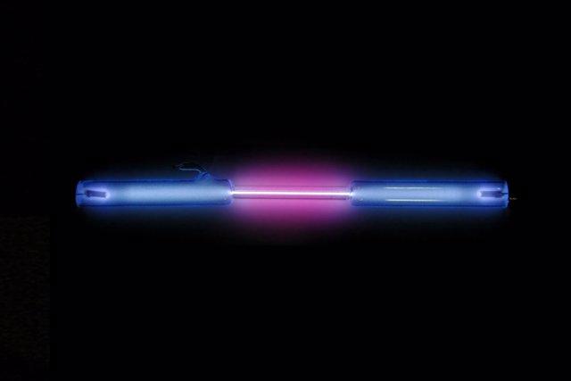 En color violeta, emisión de hidrógeno en un tubo de descarga de gases.