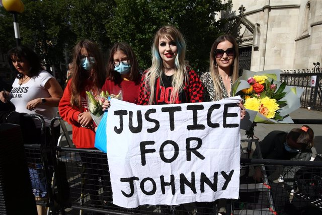 28 July 2020, England, London: Fans of US actor Johnny Depp hold a sign outside the High Court for the final day of hearings in his libel case against the publishers of The Sun and its executive editor, Dan Wootton. Photo: Yui Mok/PA Wire/dpa