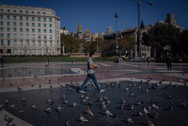 Un hombre camina por la Plaza de Cataluña en la primera mañana después del toque de queda en Barcelona, Catalunya (España), a 26 de octubre de 2020.