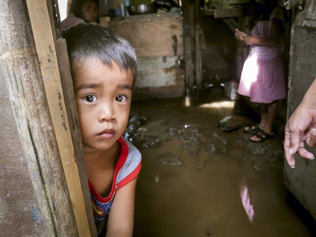 Un niño en una casa inundada por el paso del tifón 'Goni' en Batangas (Filipinas)