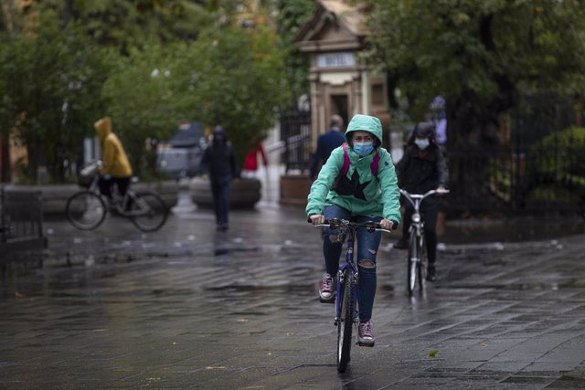 Varias personas circulan en bicicleta durante una jornada de lluvia. En Sevilla (Andalucía, España), a 22 de octubre de 2020.
