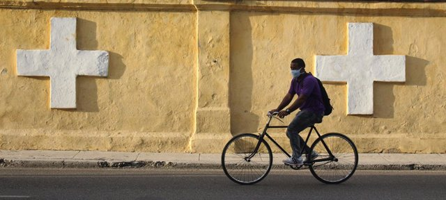30 August 2020, Cuba, Havana: A man rides his bicycle along the wall of Havana's Colon Cemetery, a curfew in Havana will be imposed from 1 to 15 September 2020 due to an increase in new coronavirus cases. Photo: Guillermo Nova/dpa