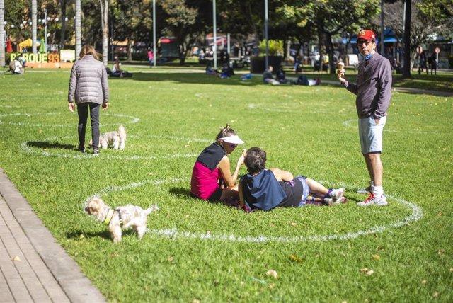 Un grupo de personas mantienen las distancias de seguridad marcadas en un parque de Bogotá, Colombia.