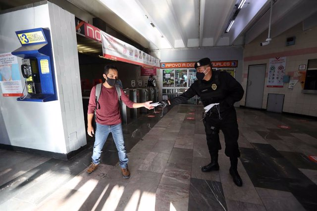 16 June 2020, Mexico, Mexico City: A police officer hands out a mouth-guard to a man at a subway station as part of the Mexican government plan to prevent the spread of the coronavirus (COVID 19) pandemic across the country. Photo: -/El Universal via ZUMA