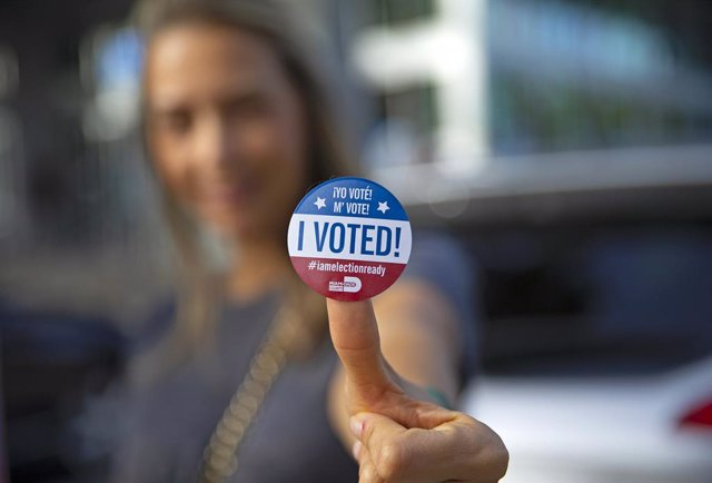 28 October 2020, US, Aventura: A woman poses for a picture with her vote sticker after casting her ballot during early voting for US Presidential election, 2020 at Northeast Dade - Aventura Branch Library. Photo: David Santiago/TNS via ZUMA Wire/dpa