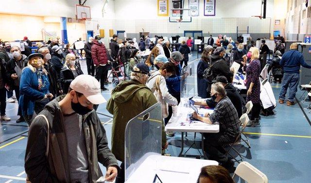 Electores estadounidenses votando con mascarilla por anticipado en Nueva York