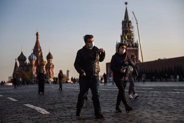 Ciudadanos pasenado por la Plaza Roja de Moscú