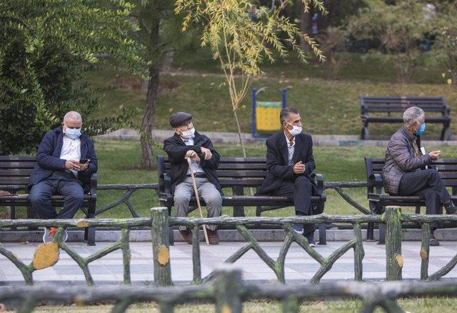 Hombres con mascarilla en un parque de Teherán