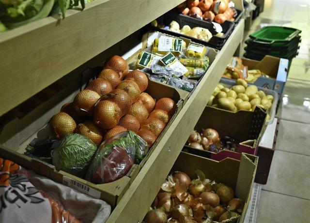 Verduras variadas: repollo, cebollas, maíz y patatas en un mercado de Madrid.