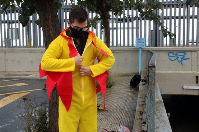 Pla mitjà del còmic Guillem Estadella emprovant-se un vestit de pollastre abans de fer el seu xou en un tren de Rodalies, el 4 de novembre del 2020 (horitzontal)