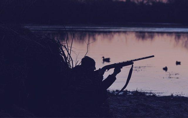Pla general d'un caçador preparat per disparat en una llacuna, de nit. Imatge del novembre del 2020 (horitzontal)