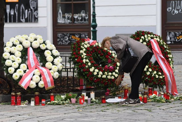 04 November 2020, Austria, Vienna: A woman lays flowers at a memorial site near the scene of the terror attack which happened on Monday evening that at least killed five people, including one perpetrator shot by police, though it remains unclear whether h