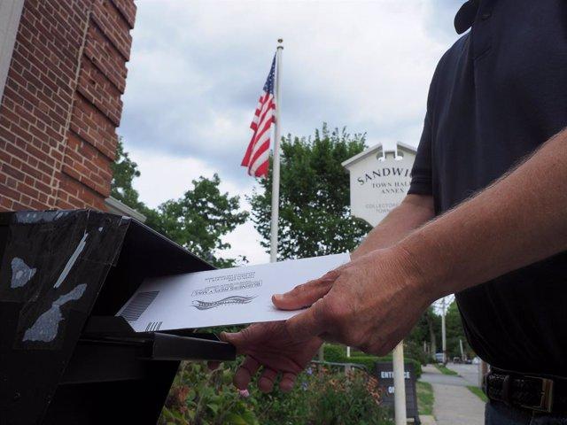 Un home deposita el seu vot postal a las elecciones dels Estats Units.