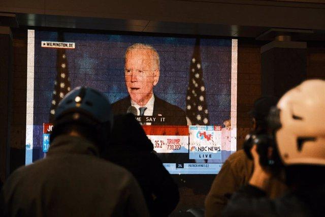 Un grupo de personas observa el discurso de Joe Biden en Washington la noche electoral