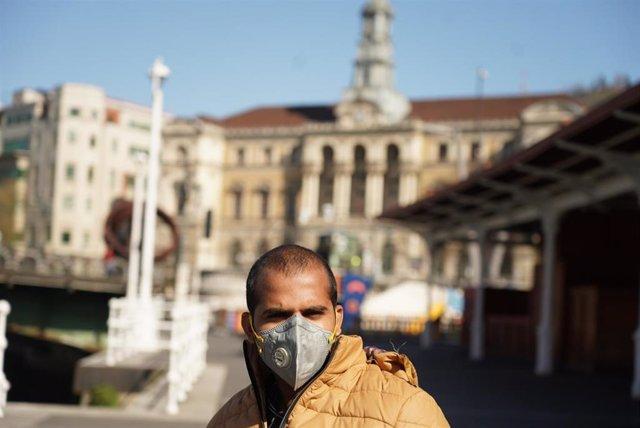 Un hombre pasea protegido con mascarilla por Bilbao tras el anterior anuncio de Estado de Alarma en España por el avance de coronavirus