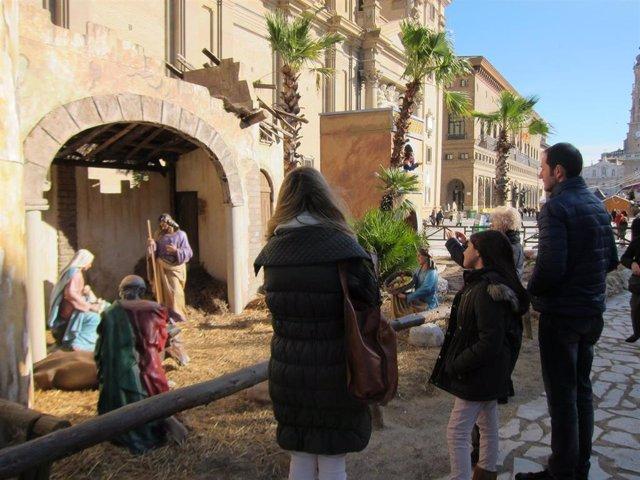 Una familia visita el belén monumental de la Plaza del Pilar
