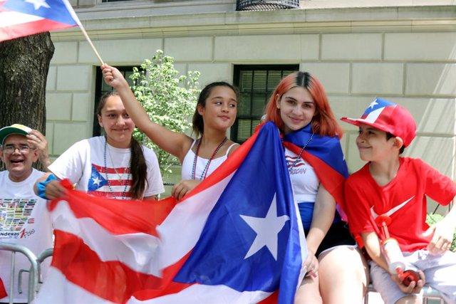 Varios jóvenes con la bandera de Puerto Rico.